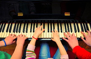Three kids playing piano. Shallow DOF.